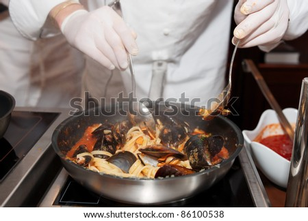Chef frying mussels with pasta on commercial kitchen in restaurant