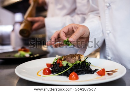 Chef garnishing meal on counter in commercial kitchen