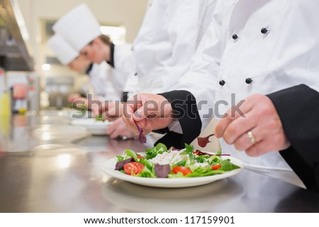 Chef garnishing salads in the kitchen with others garnishing their salads