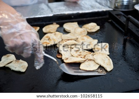 Chef getting chicken breasts of the grill for serving.