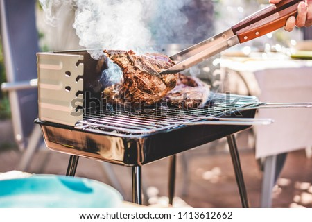 Chef grill t-bone steaks at barbecue dinner outdoor - Man cooking meat for a family bbq meal outside in backyard garden - Summe lifestyle, food and sunday time concept - Focus on tongs