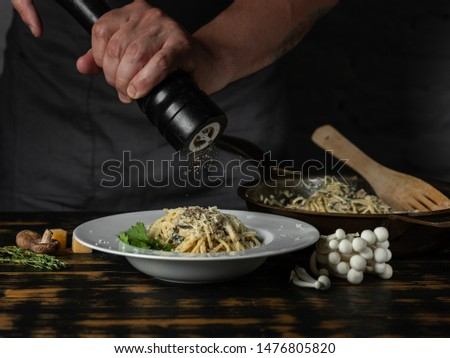 Chef hands adding paper in dish and cooking Italian pasta carbonara with cheese parmesan and white creamy sauce on wooden table background.