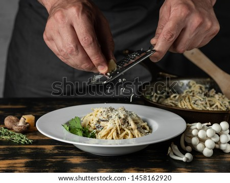 Chef hands cooking Italian pasta carbonara with cheese parmesan and white creamy sauce on wooden table background.