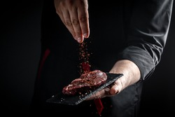 Chef hands cooking meat steak and adding seasoning in a freeze motion. Fresh raw Prime Black Angus beef rump steak. banner, menu recipe.