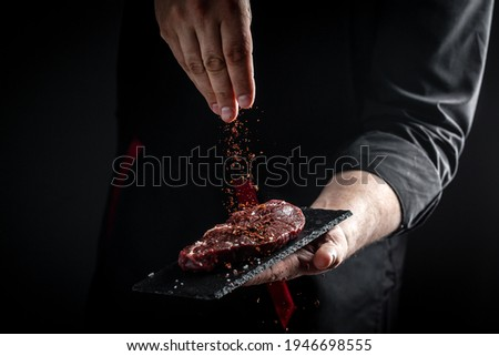 Chef hands cooking meat steak and adding seasoning in a freeze motion. Fresh raw Prime Black Angus beef rump steak. banner, menu recipe. Stockfoto ©