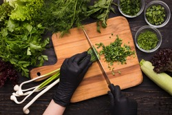 Chef hands in black gloves cutting spring onion on wooden board, kitchen table with fresh organic vegetables, top view