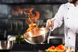 Chef hands keep wok with fire. Closeup chef hands cook food with fire. Chef man burn food at professional kitchen.