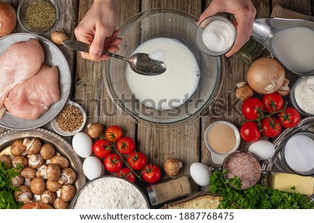 Chef hands pours some salt into glass bowl with milk for preparing dough on variety of ingredients background. Concept of cooking process. Backstage of preparing meat pie. View from above. Photo stock ©