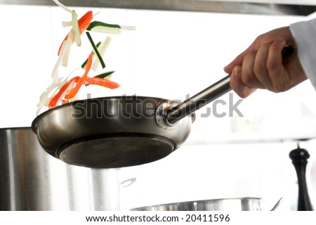 Chef hands with frying pan on professional kitchen