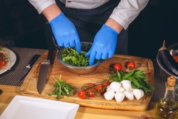 Chef hands with gloves cooked. Chef  is cooking a  gourmet dish - mozzarella with basil, cherry tomatoes and arugula.