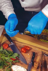 Chef hands with gloves cooked. Chef  is cooking a  gourmet dish - mozzarella with basil, cherry tomatoes and arugula. Chef poured olive oil