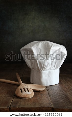 Chef hat and wooden spoons on wooden table - stock photo