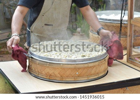 Chef hold hot steaming pot with a steamed pork dumpling and steam, chinese traditional menu, foodstuff on street food restaurant #1451936015