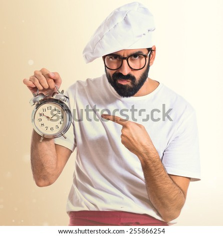Chef holding a clock over ocher background #255866254