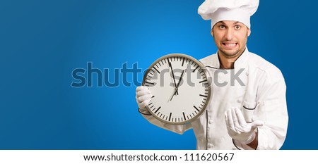 Chef Holding A Wall Clock On Blue Background