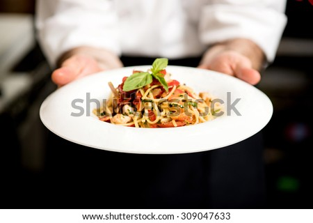 Chef holding hot spaghetti to serve in the restaurant