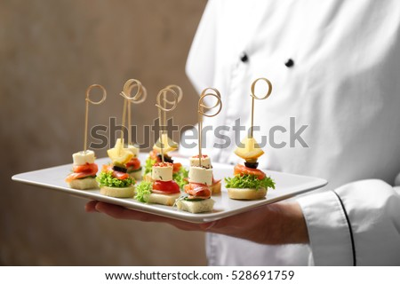 Shutterstock Chef holding plate with assorted canapes closeup