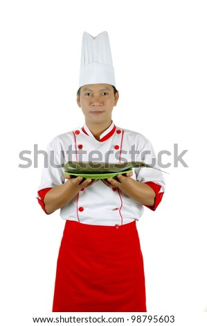 chef holding raw fish on a green plate isolated on white background
