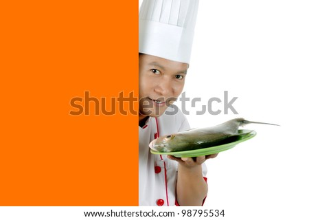 chef holding raw fish on a green plate with orange blank space isolated on white background - stock photo