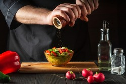 Chef in a restaurant kitchen adds peppers to a fresh vegetable salad. Close-up of a cook hands holding a mill. Cooking healthy and tasty food