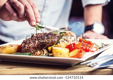 Chef in hotel or restaurant kitchen cooking only hands. Prepared beef steak with vegetable decoration. Toned photo.