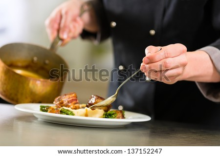 Chef in hotel or restaurant kitchen cooking, only hands to be seen, he is working on the sauce for the food as saucier