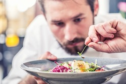 Chef in hotel or restaurant kitchen preparing meal vegetable salad with goat cheese and decorates the food with her hands.