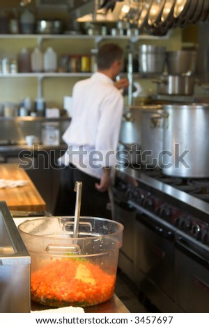 chef in restaurant kitchen, focus on foreground