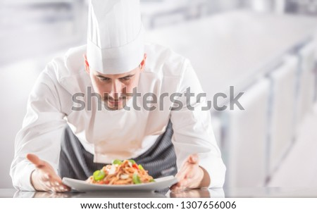 Chef in restaurant kitchen prepares and decorates meal with hands. Cook preparing spaghetti bolognese.