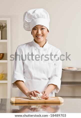 Chef  in toque and chef?s whites kneading dough in commercial kitchen - stock photo