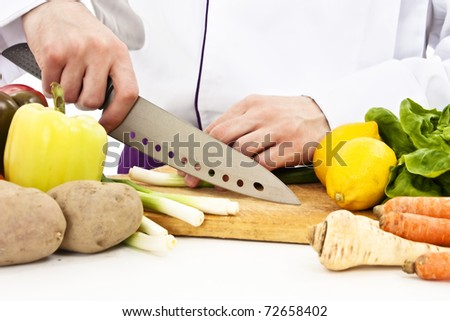Chef in uniform cuts the vegetables. Isolated on white background
