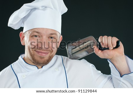 Chef in uniform with a kitchen knife smiling and looking at camera