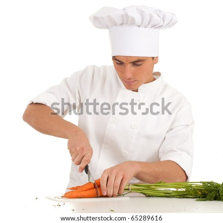 chef in white uniform and hat with knife cutting bunch of carrots