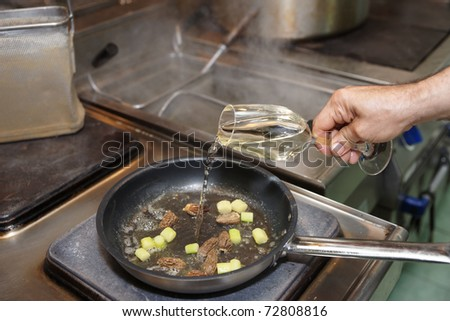 Chef is adding white wine in pan with vegetables and morels