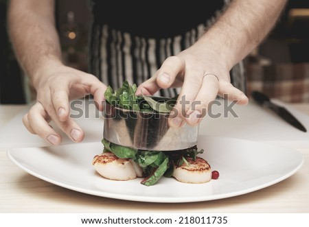 Chef is cooking appetizer with sea scallops and salad mix, toned image