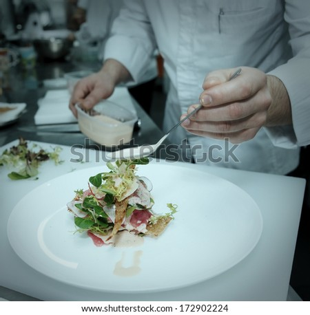 Chef is cooking fish appetizer on professional kitchen, toned, vignetting added