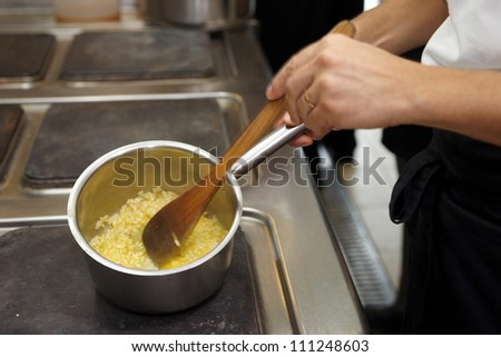Chef is cooking risotto on professional kitchen