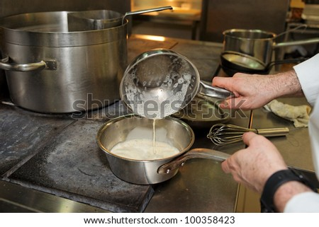 Chef is cooking sauce on electric stove, professional kitchen