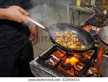 Chef is cooking seafood dish stir fry method