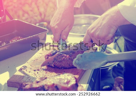 Chef is cutting meat at outdoor kitchen, toned image