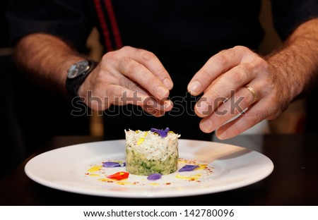 Chef is decorating delicious appetizer with flowers