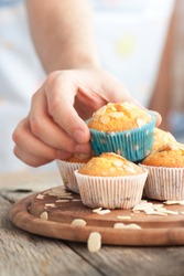 Chef is decorating delicious organic muffins. Almond and cherry cup cakes in natural setting.