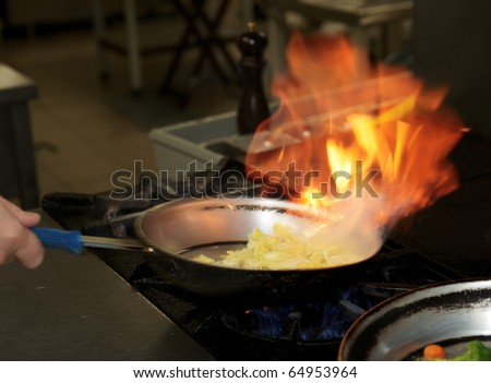 Chef is making flambe sauce on restaurant kitchen