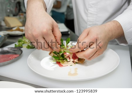 Chef is making tuna carpaccio in a restaurant