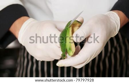 Chef is peeling avocado