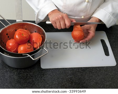 Chef is peeling boiled tomatos