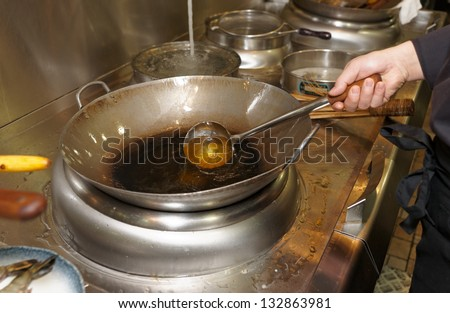 Chef is pouring cooking oil in wok at commercial kitchen