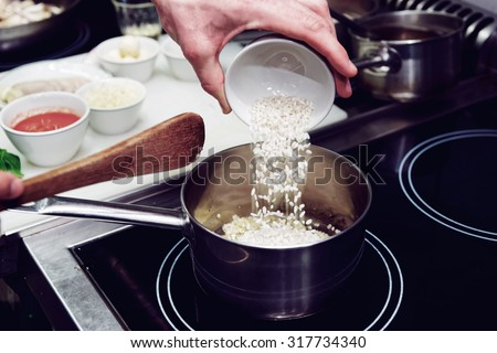 chef is pouring rice in stewpan ...