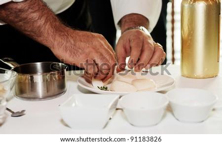 Chef is preparing mussels on a restaurant kitchen
