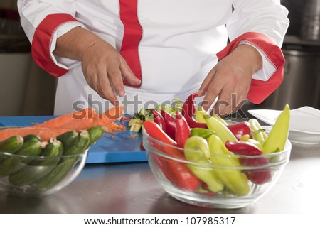 chef is preparing vegetable salad from a cabbage, tomato, cucumbers, carrot, parsley